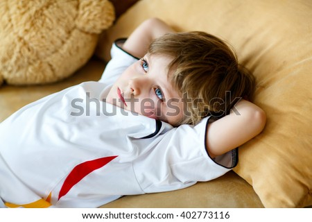 Little blond preschool kid boy after watching soccer european cup game on tv. Sad child about lost game of his football team. Champions league concept. - stock photo