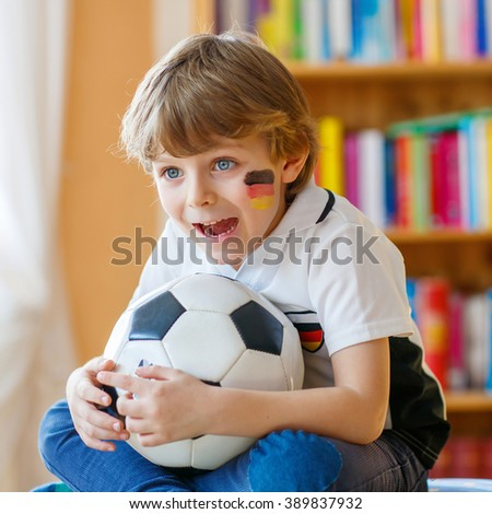 Little blond preschool kid boy with ball watching soccer european cup game on tv. Funny child fan having fun and cheering winning football team. Champions league concept.