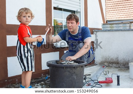 Little blond toddler boy helping his father with renovation of home - stock photo