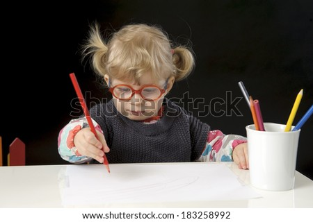 little blond toddler girl making a drawing, black background - stock photo