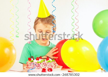 Little blonde boy in festive cap looking at the birthday cake - stock photo