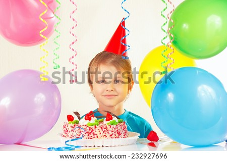 Little blonde boy in festive hat with a birthday cake and balloons - stock photo