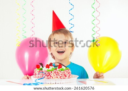 Little blonde boy in holiday cap with a birthday cake and balloons  - stock photo