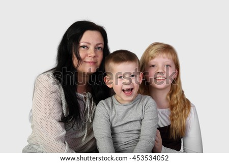 Little blonde girl and toothless boy with brunette woman on gray background - mother, son and daughter - family relations and love concept - stock photo