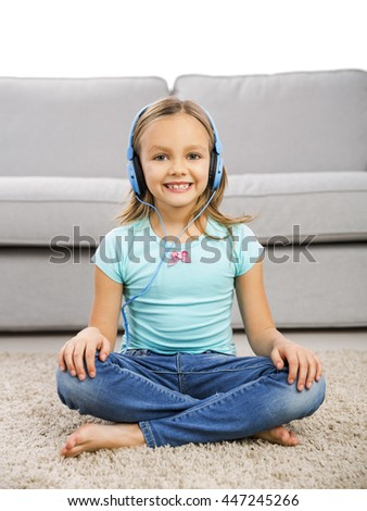 Little blonde girl at home listen music with headphones - stock photo