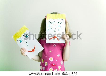Little blonde girl holding happy and sad face masks symbolizing changing emotions - stock photo
