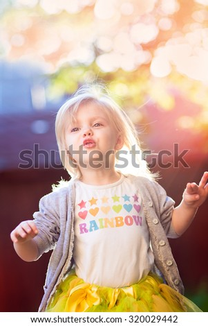 little blonde girl in a skirt tutu in a beautiful sunlight - stock photo