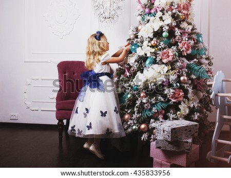 Little blonde girl in beautiful dress decorating Christmas tree at home - stock photo