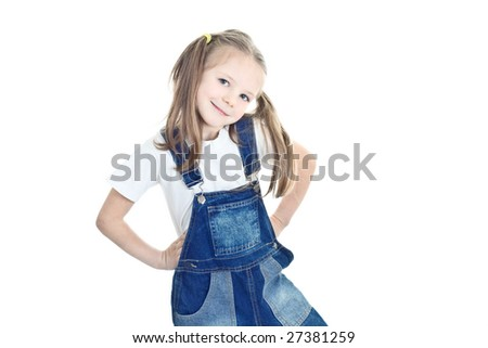 little blonde girl in blue overalls putting her hands on her hips - stock photo