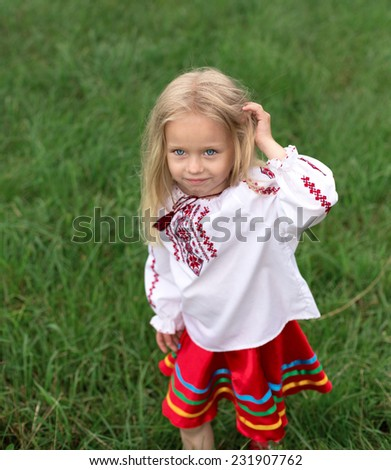 little blonde girl in ukrainian national costume are playing with her hair - stock photo