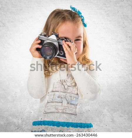 Little blonde girl photographing over textured background   - stock photo