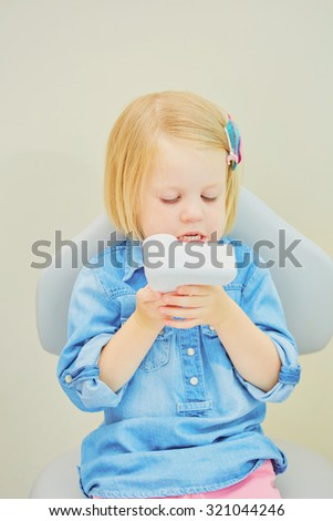 Little blonde girl sitting in the dentists office - stock photo