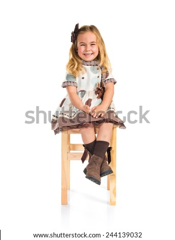 Little blonde girl sitting on chair - stock photo