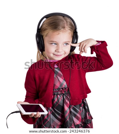 Little blonde girl smiling listening to music on smart phone mobile device with headphones - stock photo