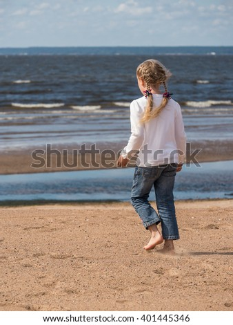 Little blonde girl walking along sand beach