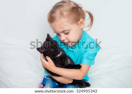 little blonde girl with pigtails in a blue shirt on a white couch watching a black cat and smiling - stock photo