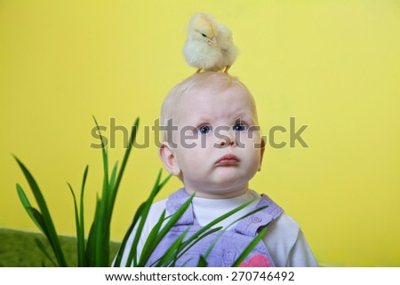 little blonde girl with yellow chicken on her head  - stock photo