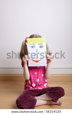 Little blonde girls holding happy face mask - stock photo