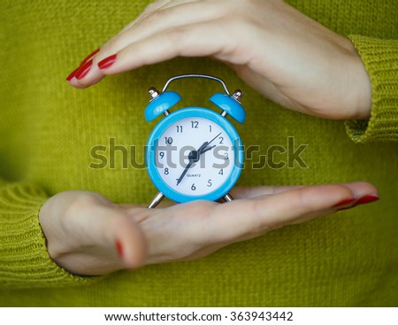 Little blue alarm clock in the hands of woman, the concept of saving time