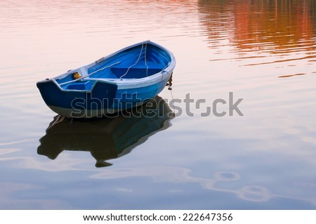 LIttle boat adrift on the water while sunset. - stock photo