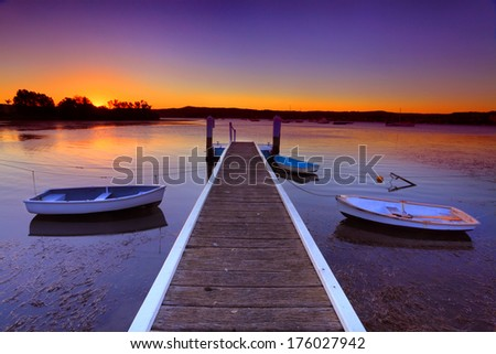 Little boats moored to a jetty at sunset.This is a quiet cove on the Brisbane Waters, Central Coast Australia - stock photo