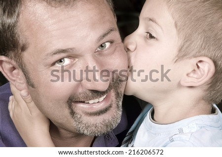 Little bond boy giving a kiss to his dad  - stock photo
