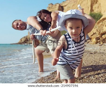 Little boy against parents competing at the beach. Summer vacation - stock photo