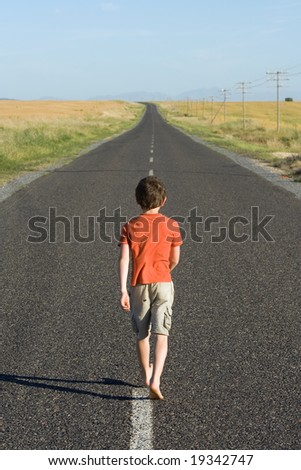 Little boy, aged eight, wearing a red shirt, waling down a tarred road towards the distant horizon