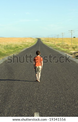 Little boy aged eight, wearing a red shirt, walking down a tarred road, looking sad