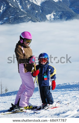 little boy and a woman in the high snowy cloudy mountains  in   winter - stock photo