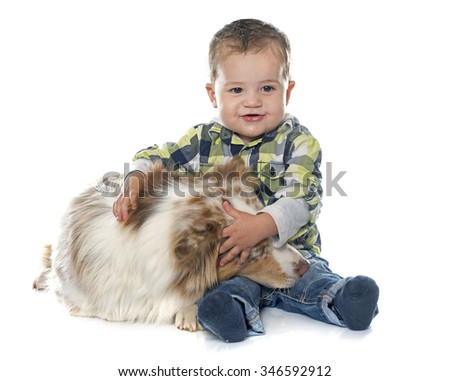 little boy and dog in front of white background - stock photo