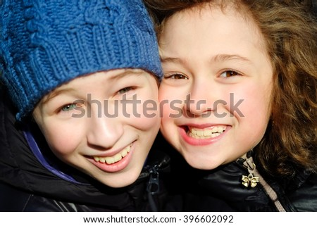 Little boy and girl close-up portrait smiling and playing outside. Portrait of happy kids, children, brother and sister laughing and having fun. - stock photo