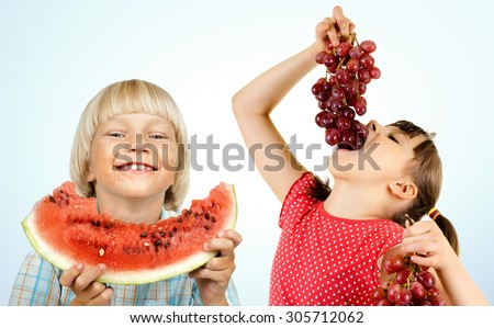 little boy and girl , eating fruit and smile, on light blue background - stock photo