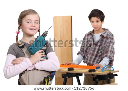 little boy and girl in a craftsman workshop - stock photo