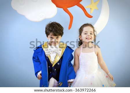 Little boy and girl in costumes are in a school play or ready for halloween enjoying the day against blue background. - stock photo