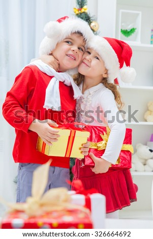Little boy and girl in Santa outfits for Christmas hug - stock photo