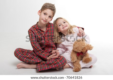 Little boy and girl in their pajamas with a teddy bear stock photo