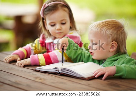 little boy and girl learning to write