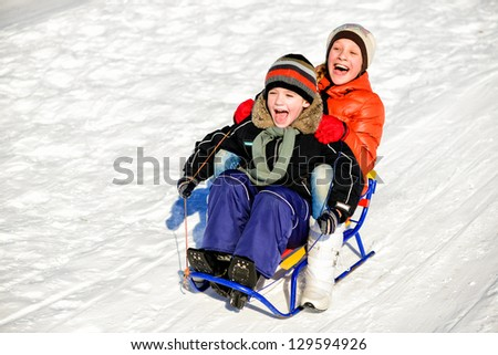 Little boy and girl on sleigh, winter games