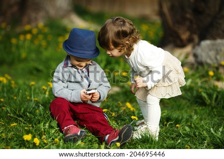 little boy and girl playing with mobile phone - stock photo
