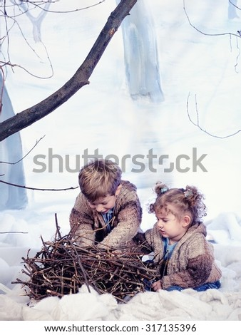 Little boy and girl plays in studio snow forest background - stock photo