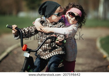little boy and girl ride bike outdoors - stock photo