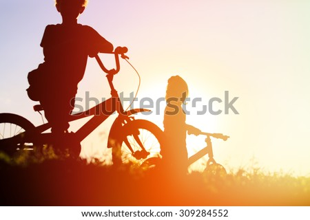 little boy and girl riding bikes at sunset, active kids sport - stock photo