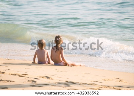 Little boy and girl sitting on the sand, sitting together in the sand looking at the sea, Blurred background, Film simulation - stock photo