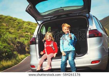 little boy and girl travel by car on road in nature