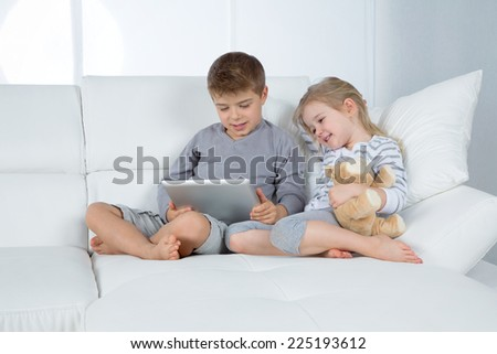 little boy and girl watching movie on grey tablet - stock photo