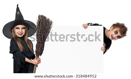 Little boy and girl wearing halloween costume with broom and blank board on white background - stock photo