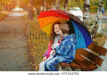 Little boy and girl whispers and sitting on the wooden bench on the autumn street.