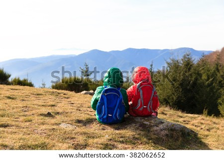 little boy and girl with backpacks having rest in mountains - stock photo
