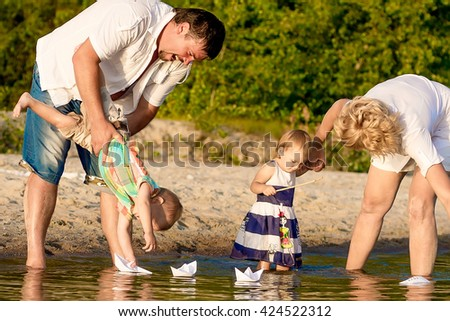 little boy and girl with parents launch paper boats on the beach in summer.
